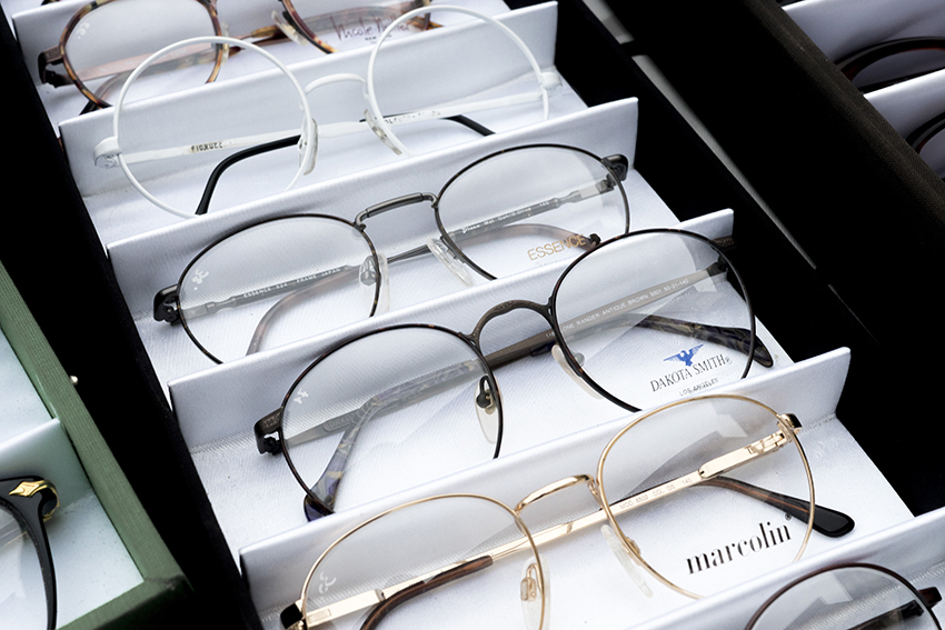 Multiple pairs of metal, round framed glasses in a white display case.